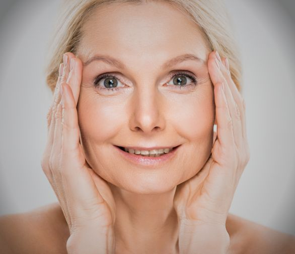 Woman holding her face between her hands smiling