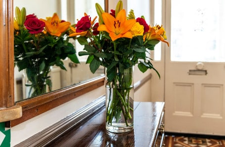 Glass vase with orange and red flowers in an entrance hallway