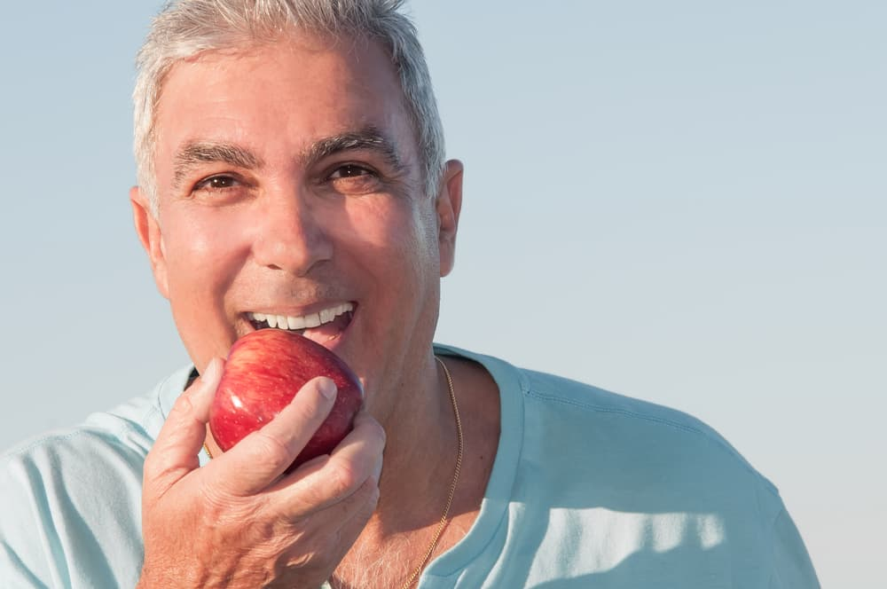 Man smiling and biting into an apple after dental implant