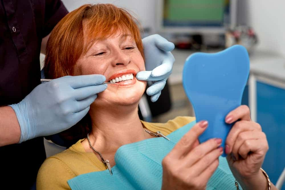 Woman sat in a dentist's chair examining dental implants with mirror