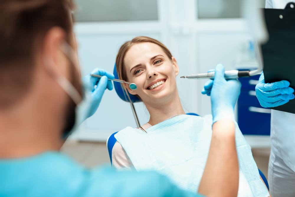 A young woman sits in a dental chair and smiles.